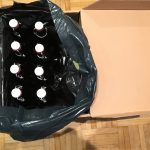 Acht Flaschen im dunklen Beutel in einer Kiste
